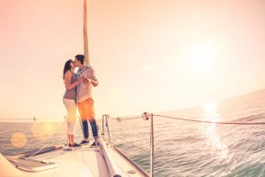 Rich young couple in love on sailboat kissing at sunset