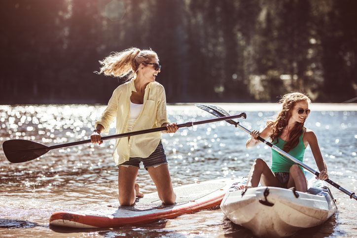 Two Girl Friends Paddle Boarding (sup) on Lake